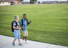 Two diverse school kids walking home together after school. And talking together. Back to school photo of diverse school children wearing backpacks in the Stock Photography