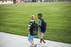 Two diverse school kids walking and talking together on the way to school. Back to school photo of diverse school children wearing backpacks in the school yard Royalty Free Stock Image