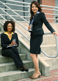 Two Diversity Businesswoman. African american and asian business women are talking by stair stock photography