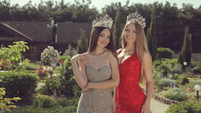 Two divinely beautiful young girls in evening. Gowns and crowns smile standing in green park stock video