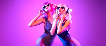 Two DJ Fitness Woman In Colorful Neon Light. Disco Royalty Free Stock Photo