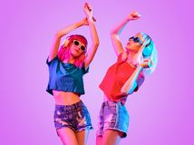 Two DJ Girl Hipster with Fashion Hairstyle Dance. High Fashion DJ Girl. Two Young Hipster in Trendy Headphones with Pink Blond Hairstyle Dance. Beautiful Sexy Royalty Free Stock Image