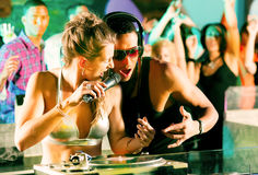 Two DJs in disco club, crowd background stock images