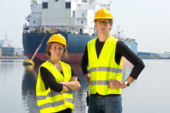 Two Dockers. A men and a woman, posing in front of a huge cargo ship, moored off at an anchor buoy in an industrial harbor Stock Images