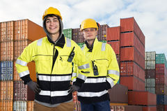 Two Dockers. Two happy harbor workers posing in front of a huge stak of containers Stock Images