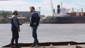Two dockers, coworkers and colleages shake hands in Shipping cargo port.  stock video footage