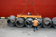 Two dockers fix a cargo of a wire for loading Stock Images