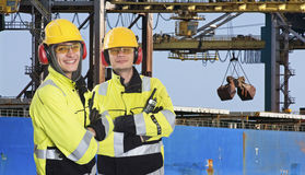 Two dockers at an Industrial Harbor. Two dockers, coworkers and colleages, wearing the same outfit, posing in front of a large transport ship, where raw Royalty Free Stock Photos