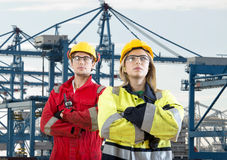 Two dockers. Two tough looking dockers in safety clothing posing in front of a huge container terminal Royalty Free Stock Photo