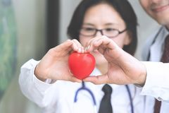 Two docter holding a red heart, health care concept. Two docter holding a red heart, health care concept stock image