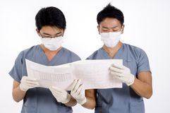 Two Doctors. Two young doctors examine a printout from an electrocardiogram Stock Photography