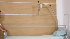 Two doctors arranging a hospital room. They are pulling a hospital bed in the room stock footage