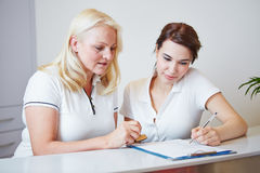 Two doctors assistants filling out form. At the reception with a pen royalty free stock image