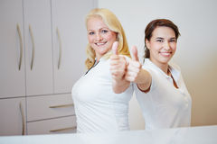 Two doctors assistants holding thumbs up. Two happy doctors assistants holding their thumbs up stock photography
