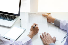 Two doctors being discussing patient history in an office pointing to a clipboard with document paper as they make a diagnosis or stock photography