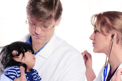 Two doctors caring for scared child patient Stock Photos