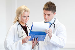 Two doctors with a clipboard. And thinking Stock Images