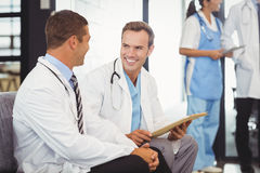Two doctors with clipboard and discussing Royalty Free Stock Images