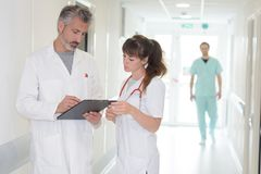 Two doctors with clipboard walking along hospital corridor. Doctors royalty free stock image