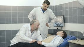 Two doctors conduct an examination with patient. 4K. Two doctors conduct an examination with patient 4K stock video footage