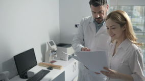 Two doctors consulting in medical office. Teamwork and cooperation. Male doctor holding medical papers and discussing diagnosis with a female colleague in the stock footage