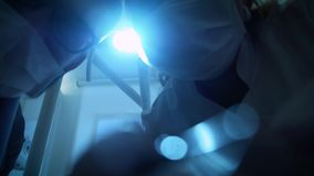 Two doctors of the dentist in Mask is Smiling, Holding a Mouth Mirror and Hook, Turns the Light of Dental Lamp On. Lights Into a Patient`s Mouth, Standing Upon stock video footage