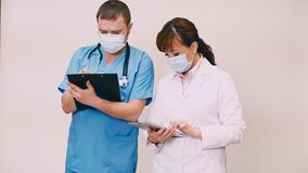 Two doctors discuss diagnoses. Make tips stock video footage