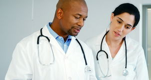 Two doctors discussing with the clipboard. Two doctors discussing with clipboard in the hospital stock footage