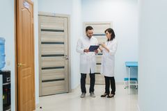 Two doctors discussing diagnosis while walking royalty free stock photography