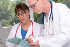 Two doctors discussing about medical report Stock Photos