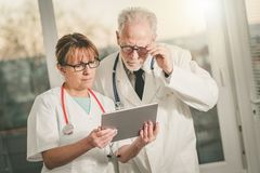 Two doctors discussing about medical report on tablet royalty free stock photos