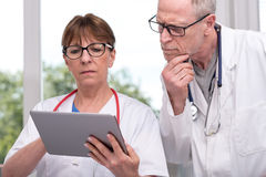 Two doctors discussing about medical report on tablet Stock Images