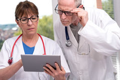 Two doctors discussing about medical report on tablet Royalty Free Stock Photo