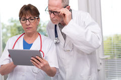 Two doctors discussing about medical report on tablet Stock Photography