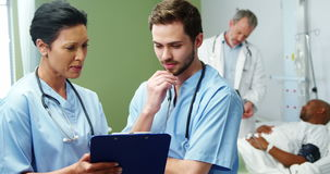 Two doctors discussing over digital tablet. At the hospital stock footage