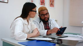 Two doctors discussing X-ray image on tablet stock video