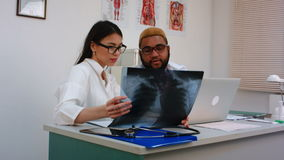 Two doctors discussing X-ray image while using computer. Professional shot on BMCC RAW with high dynamic range. You can use it e.g. in your commercial video stock video