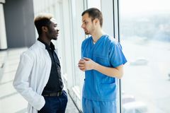 Mixed race Two doctors discussing results of the analysis in modern hospital. Two doctors discussing results of the analysis in hospital stock photos