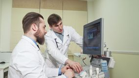 Two doctors discussing ultrasound scanning results of a patient. Handsome medical worker examining sonogram results with his colleague. Medicine, health survey stock video footage