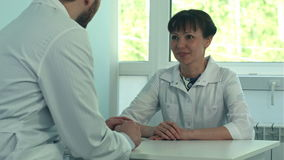 Two doctors discussing and working together in a medical office stock footage
