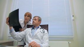 Two doctors examining patients X-rays in office. Doctors in a meeting examining xray. Serious doctors looking together at an xray. Hospital, profession, people stock video