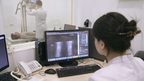 Two doctors examinting patient using mri. Doctor looking at screen with different images from mri stock video
