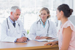 Two doctors with a female patient Stock Images