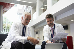 Two Doctors Having Meeting In Hospital Reception Area royalty free stock images