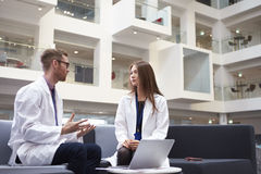 Two Doctors Having Meeting In Hospital Reception Area royalty free stock image
