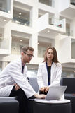 Two Doctors Having Meeting In Hospital Reception Area royalty free stock photography