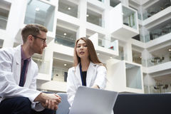 Two Doctors Having Meeting In Hospital Reception Area stock image