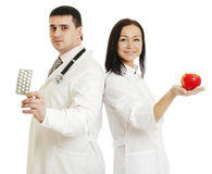 Two doctors holding apple and pills - Stock Image Royalty Free Stock Photography