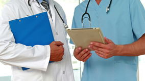 Two doctors holding clipboard in medical office stock video