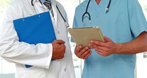 Two doctors holding clipboard in medical office. VIdeo of two doctors holding clipboard in medical office stock video